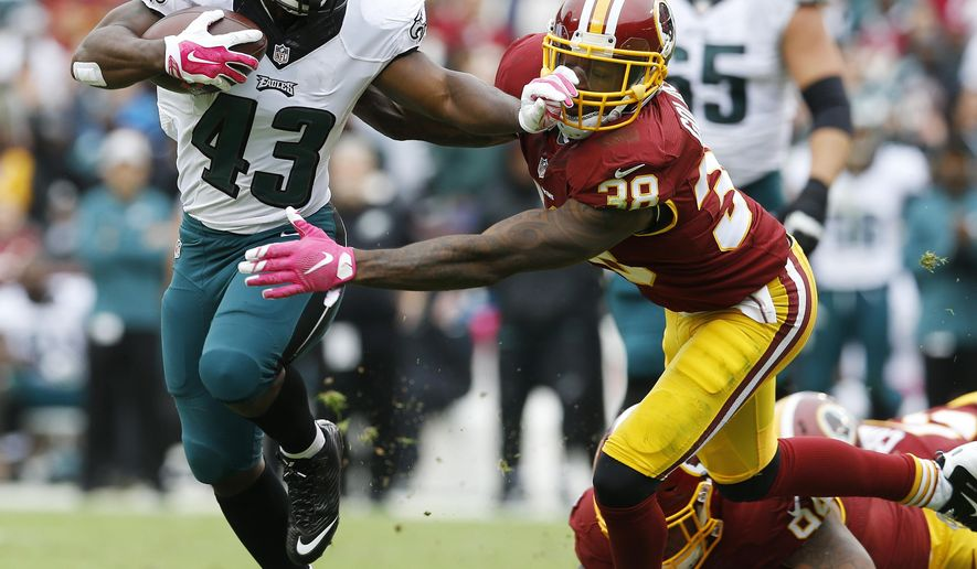 Philadelphia Eagles running back Darren Sproles (43) tries to elude Washington Redskins free safety Dashon Goldson (38) during the first half of an NFL football game in Landover, Md., Sunday, Oct. 4, 2015. (AP Photo/Patrick Semansky)