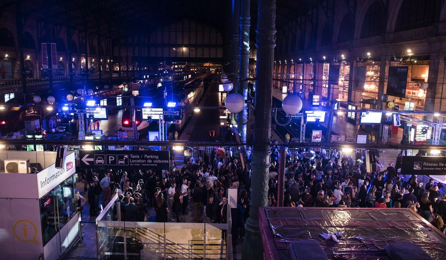 "Participants of a silent disco dance with headsets at the railway station Gare du Nord, turned into a giant nightclub, during the 14th edition of the Paris cultural event ""Nuit Blanche,"" or ""Sleepless Night,"" in Paris early Sunday, Oct. 4, 2015. (AP Photo/Kamil Zihnioglu)"