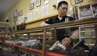In this Wednesday, Sept. 30, 2015 photo, High Bridge Arms general manager Steve Alcairo reaches into a display case of handguns while being interviewed in San Francisco. High Bridge Arms, the last gun store in San Francisco, is scheduled to close on Oct. 31, 2015. (AP Photo/Jeff Chiu)