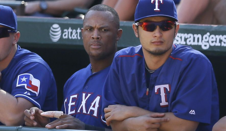 Texas Rangers pitcher Yu Darvish, right, of Japan watches from the dugout with teammate Adrian Beltre during a baseball game against the Los Angeles Angels in Arlington, Texas, Sunday, Oct. 4, 2015. (AP Photo/LM Otero)