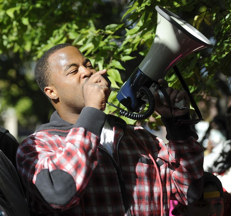 """Rashad Turner, the leader of the St. Paul chapter of """"Black Lives Matter"""", speaks to supporters before they begin their march near the rout of the Medtronic Twin Cities Marathon, in St. Paul, Sunday, Oct. 4 2015. (AP Photo/Craig Lassig)"""