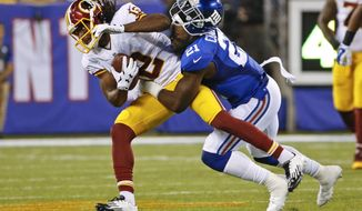 New York Giants free safety Landon Collins (21) tackles Washington Redskins wide receiver Andre Roberts (12) during the first half an NFL football game Thursday, Sept. 24, 2015, in East Rutherford, N.J. (AP Photo/Kathy Willens)