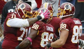 Washington Redskins wide receiver Pierre Garcon (88) is congratulated by teammates tackle Trent Williams (71) and tight end Derek Carrier (89) after scoring the winning touchdown during the second half of an NFL football game in Landover, Md., Sunday, Oct. 4, 2015. The Redskins defeated the Eagles 23-20. (AP Photo/Alex Brandon)