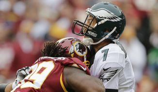 Philadelphia Eagles quarterback Sam Bradford (7) takes a shot in the chin from Washington Redskins defensive tackle Ricky Jean Francois (99) during the second half of an NFL football game in Landover, Md., Sunday, Oct. 4, 2015. (AP Photo/Mark Tenally)