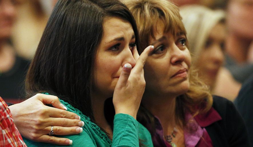 Lacey Scroggins, left, is comforted by her mother Lisa Scroggins during a church service at the New Beginnings Church of God, Sunday, Oct. 4, 2015, in Roseburg, Ore. Lacey Scroggins is a survivor of the fatal shooting at Umpqua Community College. (AP Photo/John Locher)