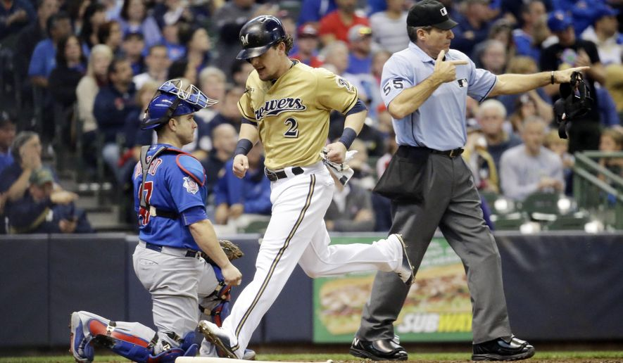 Milwaukee Brewers' Scooter Gennett scores past Chicago Cubs catcher Miguel Montero during the third inning of a baseball game Sunday, Oct. 4, 2015, in Milwaukee. Gennettn scored from second on a hit by Shane Peterson. (AP Photo/Morry Gash)