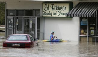 Jordan Bennett, of Rock Hill, S.C., paddles up to a flooded store in Columbia, S.C., Sunday, Oct. 4, 2015. The rainstorm drenching the U.S. East Coast brought more misery Sunday to South Carolina, cutting power to thousands, forcing hundreds of water rescues and closing many roads because of floodwaters.  (AP Photo/Chuck Burton)