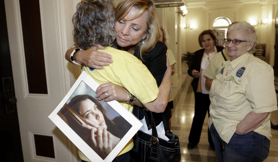 FILE - In this Sept. 9, 2015, file photo, Debbie Ziegler holds a photo of her late daughter, Brittany Maynard, as she receives congratulations from Ellen Pontac, left, after a right-to die measure was approved by the state Assembly in Sacramento, Calif. California will become the fifth state to allow terminally ill patients to legally end their lives using doctor-prescribed drugs after Gov. Jerry Brown announced Monday, Oct. 5, 2015 he signed one of the most emotionally charged bills of the year. (AP Photo/Rich Pedroncelli, File)