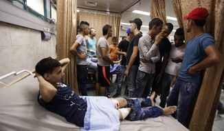 A Palestinian lies in hospital after he was wounded during an Israeli military raid in the West Bank city of Jenin, Sunday, Oct. 4, 2015. Israeli troops shot and wounded at least 18 Palestinians in violence during an arrest raid in the Jenin refugee camp, a Palestinian hospital director said. (AP Photo/Majdi Mohammed)