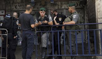 """An Israeli border policeman checks papers at the entrance to the Old City in Jerusalem on Sunday, Oct. 4, 2015. Israeli police barred Palestinians from Jerusalem's Old City on Sunday in response to stabbing attacks that killed two Israelis and wounded three others, as Israeli Prime Minister Benjamin Netanyahu vowed a """"harsh offensive"""" to counter rising violence. (AP Photo/Mahmoud Illean)"""