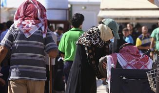 In this Thursday, Oct. 1, 2015 photo, Syrian refugees wait to sign up for a return bus to the Syrian border, at the U.N.-run Zaatari refugee camp near Mafraq, northern Jordan. Growing numbers of Syrian refugees are returning to their war-ravaged homeland from Jordan because they can't survive in exile after drastic aid cuts, can't afford to pay smugglers to sneak them into Europe or are simply homesick. (AP Photo/Raad Adayleh)
