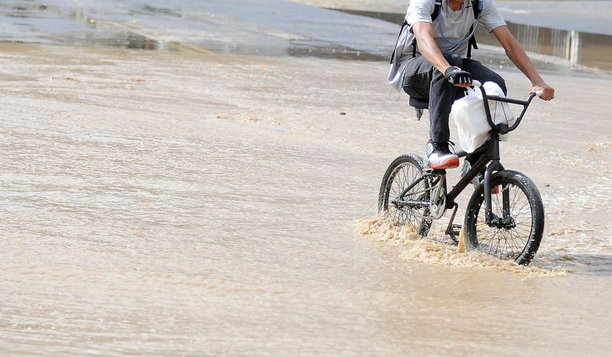 A bicyclist navigates his way through water flowing in the Oro Grande Wash near Doris Davies Park in Victorville Calif., Monday, Oct. 5, 2015. (James Quigg/The Victor Valley Daily Press via AP) MANDATORY CREDIT