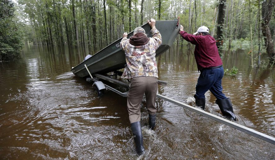Florence, S.C. residents Jackie Lee, right, and Robin Powers launch a boat before surveying the flooding to Lee's property on Roundtree Road along the Lynches River near Effingham, S.C., Tuesday, Oct. 6, 2015, where houses and cars are swamped with floodwater following record rainfall in the state. (AP Photo/Gerry Broome)