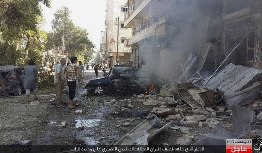 "In this Monday, Oct. 5, 2015 photo released by the Rased News Network, a Facebook account affiliated with Islamic State militants, which has been authenticated based on its contents and other AP reporting, people gather at the site of an airstrike in Al-Bab on the outskirts of Aleppo, Syria. The Britain-based Syrian Observatory for Human rights said warplanes believed to be Russian have targeted the northern town of Al-Bab that is a stronghold of the Islamic State group. The Arabic at the bottom reads, ""The destruction that was caused by airstrikes of the Crusader-Alawite coalition on the town of Al-Bab."" (Rased News Network via AP)"