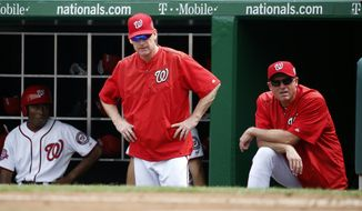 Washington Nationals manager Matt Williams, center, and bench coach Randy Knorr stand in the dugout during a baseball game against the Miami Marlins at Nationals Park, Sunday, Aug. 30, 2015, in Washington. (AP Photo/Alex Brandon)