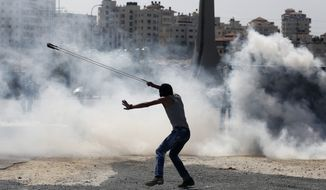 A Palestinian demonstrator uses a slingshot during clashes following a demonstration in the West Bank city of Ramallah, Monday, Oct. 5, 2015. (AP Photo/Nasser Shiyoukhi)