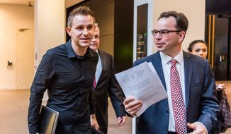 Max Schrems, left, and his lawyer Herwig Hofmann, right, walk in the hallway at the European Court of Justice in Luxembourg on Tuesday, Oct. 6, 2015. Europe's highest court has ruled in favor of an Austrian law student who claims a trans-Atlantic data protection agreement doesn't adequately protect consumers. (Geert Vanden Wijngaert)