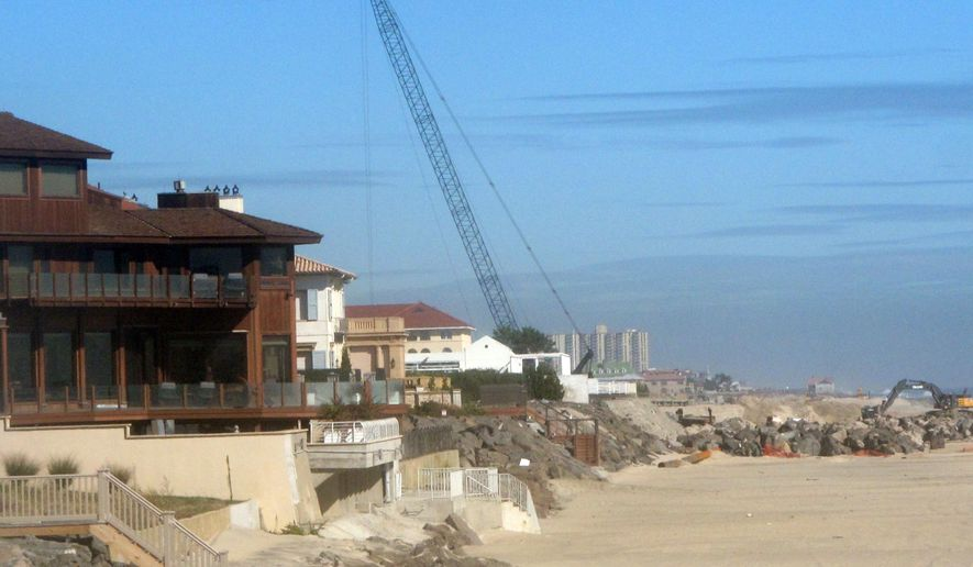 A crane operates near oceanfront homes in Deal, N.J. on Tuesday Oct. 6, 2015.  The borough of Deal is due to vote Friday on an ordinance that would restrict parking on six streets nearest the beach to residents only. They would be issued permits to display in their vehicles.  The move comes as the U.S. Army Corps of Engineers is finishing a $40 million beach replenishment project that has drastically widened Deal's beaches, work completely paid for by the federal government. (AP Photo/Wayne Parry)