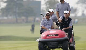 United States team assistant's Fred Couples, left, and Jim Furyk, right, drive player's Jordan Spieth and Dustin Johnson on a cart during their final practice round ahead of the Presidents Cup golf tournament at the Jack Nicklaus Golf Club Korea, in Incheon, South Korea, Wednesday, Oct. 7, 2015.(AP Photo/Lee Jin-man)