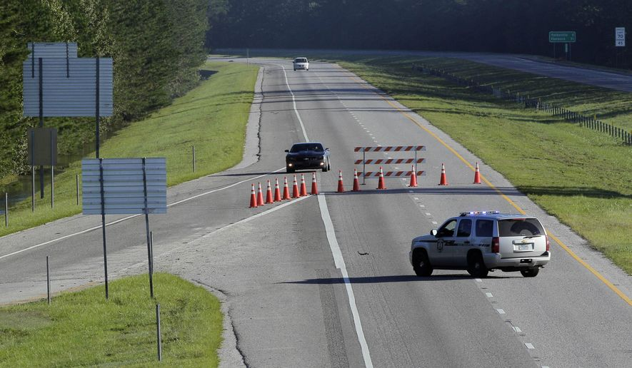 State police block a section of interstate 95 south at S.C. highway 527 near Sumter, S.C., Wednesday, Oct. 7, 2015 as road and bridge closures continue to cause transportation problems following flooding in many parts of the state. (AP Photo/Gerry Broome)