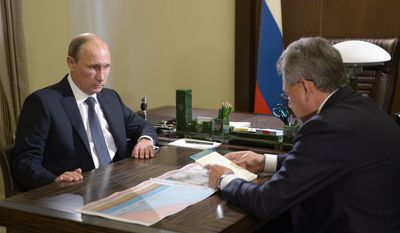 Russian President Vladimir Putin, left, listens to Defense Minister Sergei Shoigu during their meeting in the Bocharov Ruchei residence in the Black Sea resort of Sochi, Russia, Wednesday, Oct. 7, 2015. Shoigu on Wednesday told President Vladimir Putin in televised remarks that Russia on Wednesday morning carried out 26 missile strikes from four warships of its Caspian Sea flotilla. Shoigu insisted that it destroyed all the targets and did perform any strikes on civilian areas. (Alexei Nikolsky, RIA-Novosti, Kremlin Pool Photo via AP)