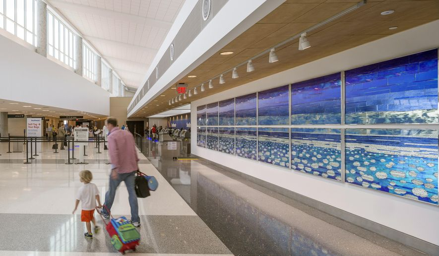 "In this Oct. 5, 2015 photo, Libbie J. Masterson's ""Ethereal Sky"" adorns a wall next to the Southwest Airlines ticket counters at Hobby Airport's new international terminal in Houston. The new concourse opens Oct. 15. (Nash Baker/Houston Chronicle via AP) MANDATORY CREDIT"