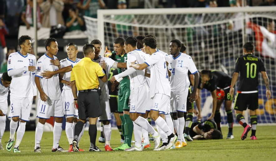 Honduras players surround the referee to argue after defender Allans Vargas was given a red card for tripping Mexico forward Marco Bueno during the first half of a CONCACAF Men's Olympic qualifying soccer match Wednesday, Oct. 7, 2015, in Commerce City, Colo. (AP Photo/David Zalubowski)