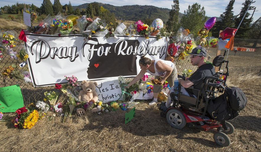 Candida Miller, left, and Brandon Snyder leave flowers at a site of a growing memorial to victims of the mass shooting at Umpqua Community College in Roseburg, Ore., Tuesday, Oct. 6, 2015. (AP Photo via Chris Pietsch/The Register-Guard)
