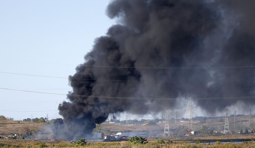 Plumes of smoke rise from northbound side of the New Jersey Turnpike extension where a tanker truck overturned and caught fire on the shoulder, Wednesday, Oct. 7, 2015, in Kearny, N.J. There were no injuries reported. (AP Photo/Julio Cortez)