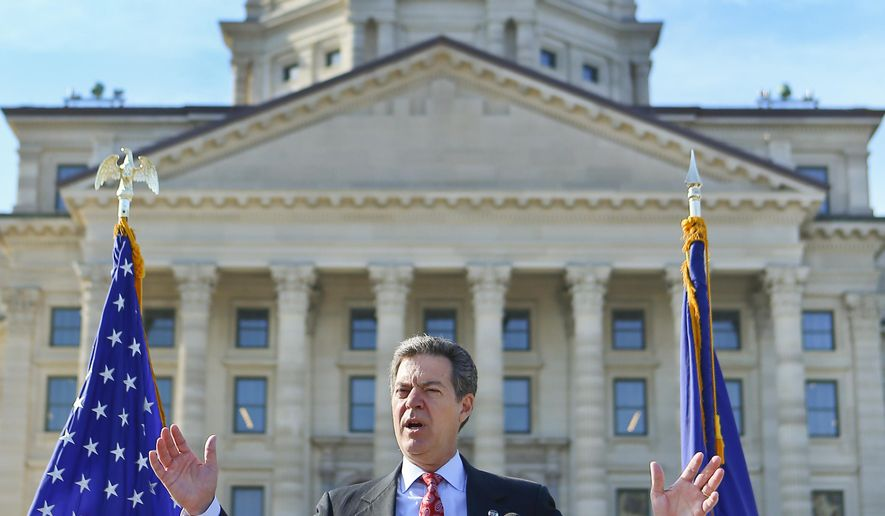 Kansas Gov. Sam Brownback addresses the crowd on Wednesday Oct. 7, 2015, during the Kansas Walk of Honor induction ceremony of President Dwight D. Eisenhower at the Kansas Statehouse in Topeka, Kan. A plaque honoring President Eisenhower was placed in the sidewalk on the North side of the capitol. The Kansas Walk of Honor features significant individuals on the state and national level who have ties to Kansas.  (Chris Neal/The Topeka Capital-Journal via AP) MANDATORY CREDIT
