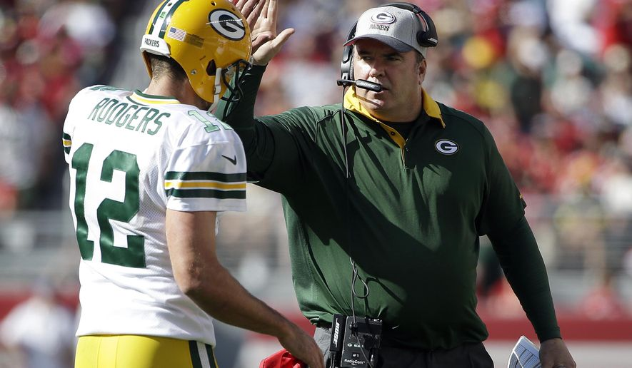 Green Bay Packers quarterback Aaron Rodgers (12) and head coach Mike McCarthy celebrate after they scored a touchdown against the San Francisco 49ers during the second half of an NFL football game in Santa Clara, Calif., Sunday, Oct. 4, 2015. (AP Photo/Marcio Jose Sanchez)
