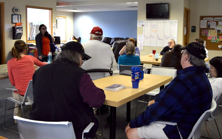 ADVANCE FOR SUNDAY, OCT. 11 AND THEREAFTER - In a Sept. 29, 2015 photo, Ashley Rowe, executive director of the Holland Drop In Center in Holland, Mich., speaks with clients about the center's budget issues after Community Mental Health of Ottawa County reduced funding by 20 percent. The center is dropping its cable TV this month to save cash. (Amy Biolchini/The Holland Sentinel via AP)