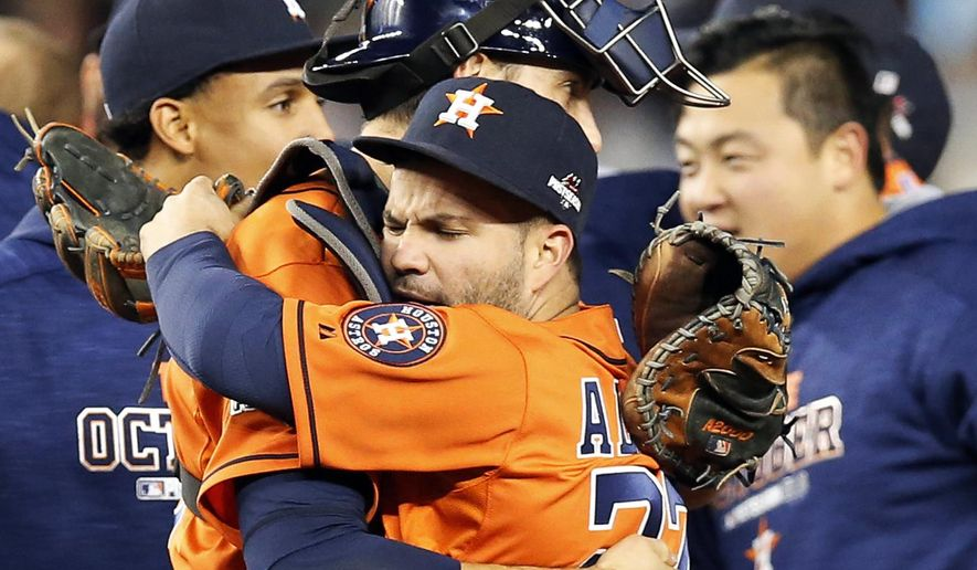 Houston Astros catcher Jason Castro, center left, embraces Astros second baseman Jose Altuve after the Astros beat the New York Yankees 3-0 in the American League wild card baseball game at Yankee Stadium in New York, Tuesday, Oct. 6, 2015. Astros center fielder Carlos Gomez is at left and Hank Conger is at right. (AP Photo/Kathy Willens)