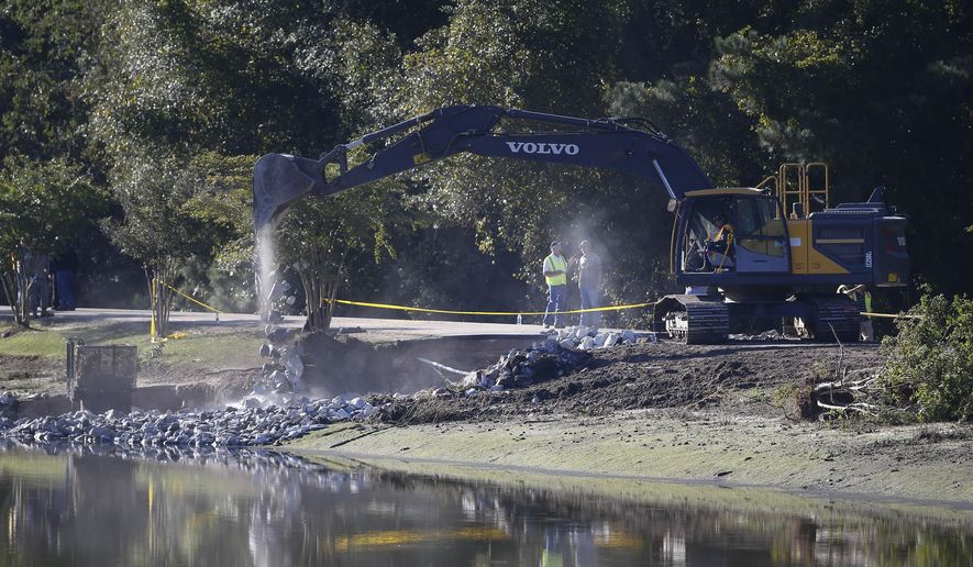 Work crews use an excavator to stabilize a dam, Wednesday Oct. 7, 2015,  in Columbia, S.C. Heavy rain has caused flooding in parts of the state. (AP Photo/John Bazemore)