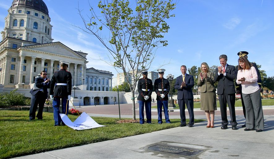 From right: Kansas first lady Mary Brownback, Gen. Victor Braden, back right, Kansas Gov. Sam Brownback, Mary Jean Eisenhower, Merrill Atwater and members of the Topeka High School Junior ROTC unveil the plaque at the Kansas statehouse honoring President Dwight D. Eisenhower on the Kansas Walk of Honor on Wednesday Oct. 7, 2015, in Topeka, Kan. A plaque honoring President Eisenhower was placed in the sidewalk on the North side of the capitol. The Kansas Walk of Honor features significant individuals on the state and national level who have ties to Kansas. (Chris Neal/The Topeka Capital-Journal via AP) MANDATORY CREDIT