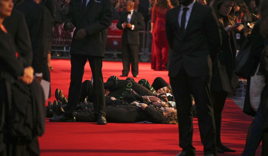 """In an echo of the suffragettes' direct-action tactics, protesters from anti-domestic violence group Sisters Uncut got past barriers and lay on the red carpet carrying signs saying """"Dead Women Can't Vote,"""" and said on Twitter they were continuing the suffragettes' struggle for women's equality, as they protest at the glitzy festival premiere for the film, Suffragette, in London, Wednesday, Oct. 7, 2015.  The film portrayal of women's suffrage, Suffragette is the opening gala of the London film festival. (Photo by Joel Ryan/Invision/AP)"""