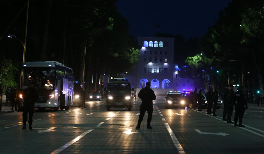 Albanian police guard the bus of the Serbian accredited media representatives after their arrival at a hotel in Tirana on Wednesday, Oct. 7, 2015, amid tough security measures for Thursday's game. Police in Albania have arrested a man who claimed to have flown a drone carrying a nationalist banner over a stadium in Serbia last year during a European qualifier, in an incident that prompted fan violence and a diplomatic spat between the two countries. (AP Photo/Hektor Pustina)