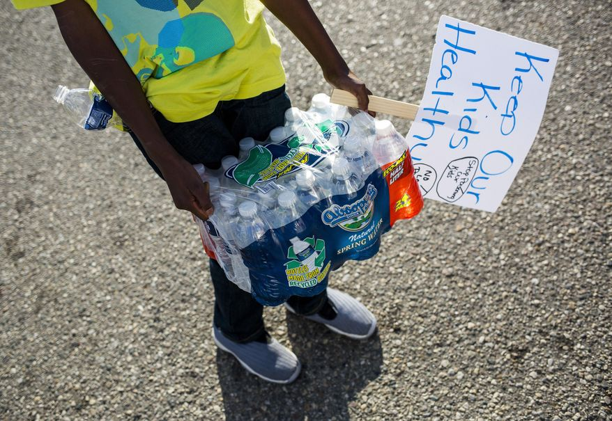 """Community leaders pass out cases of bottled water to Flint residents on Wednesday, Oct. 7, 2015, in downtown Flint, Mich. The bottle delivery was made possible by donations raised through a group's GoFundMe.com page called """"Bottles for Babies.""""   (Danny Miller /The Flint Journal-MLive.com via AP) LOCAL TELEVISION OUT; LOCAL INTERNET OUT; MANDATORY CREDIT"""