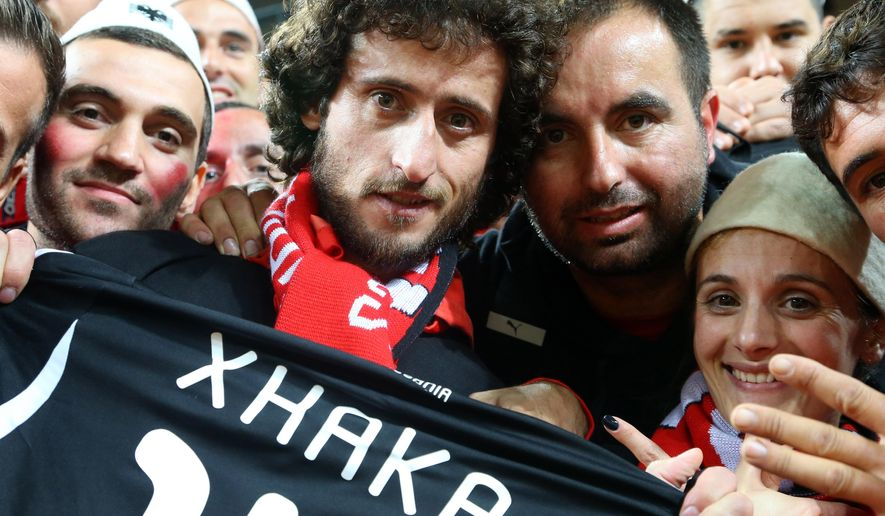FILE - In this photo taken on Friday, Sept. 4, 2015 Albanian Ismail Morinaj, 33, second left with beard who has the scarf around his neck, poses with other fans of Albanian national soccer team before a European qualifier game against Denmark in Copenhagen. Albanian police in Tirana on Wednesday, Oct. 7, 2015 say they have arrested Morinaj who claimed to have flown a drone carrying a nationalist banner over a stadium in Serbia last year during a  European qualifier, in an incident that prompted fan violence and a diplomatic  spat between the two countries. (AP Photo/Hektor Pustina, File)