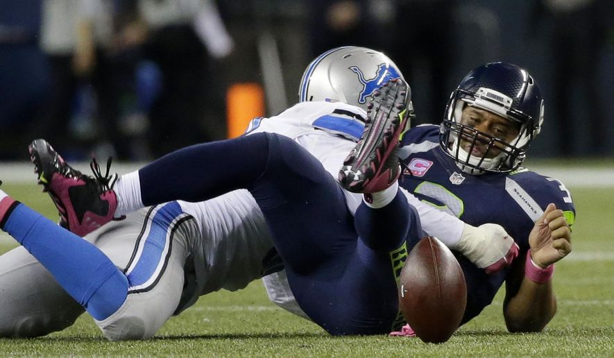 Seattle Seahawks quarterback Russell Wilson, right, watches after he fumbled in the second half of an NFL football game while being tackled by Detroit Lions defensive end Ezekiel Ansah, left, who recovered the ball on the play, Monday, Oct. 5, 2015, in Seattle. (AP Photo/Elaine Thompson)