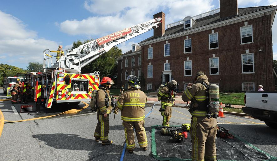 Firefighters work a smokey fire that forced the evacuation of Legislative Hall, Delaware's capitol, Wednesday, Oct. 7, 2015, in Dover, Del. Lawmakers were not in session. Dover Fire Chief Mark Hall said a generator in the basement and a closet on the second floor caught fire. (Jason Minto/The News Journal via AP)