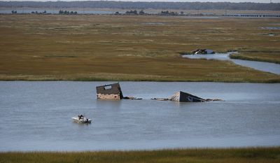 A fishing boat passes by a house that floated away in Grassy Sound during the weekend storm remains stuck in a tidal creek, Tuesday, Oct. 6 2015, in Middle Township, N.J. (Ben Fogletto/The Press of Atlantic City via AP)