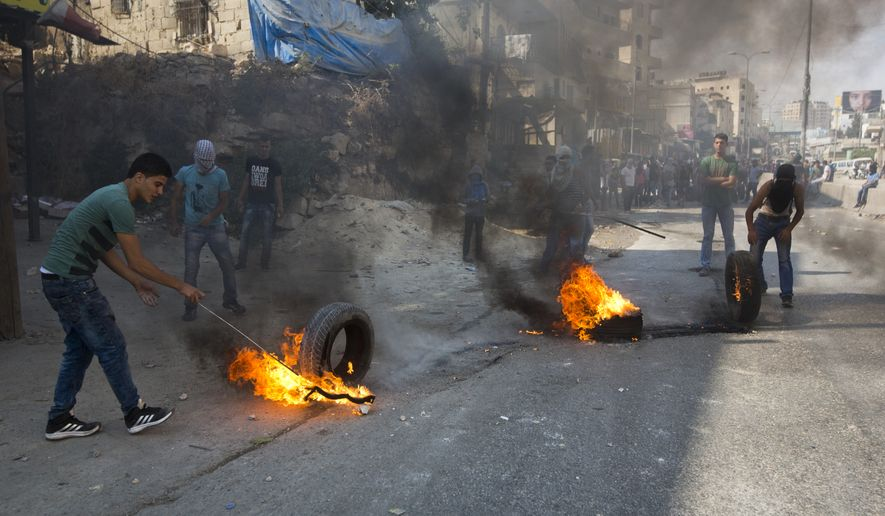 Palestinians burn tires during clashes with Israeli troops at a checkpoint between Jerusalem and the West Bank city of Ramallah. (Associated Press/File)