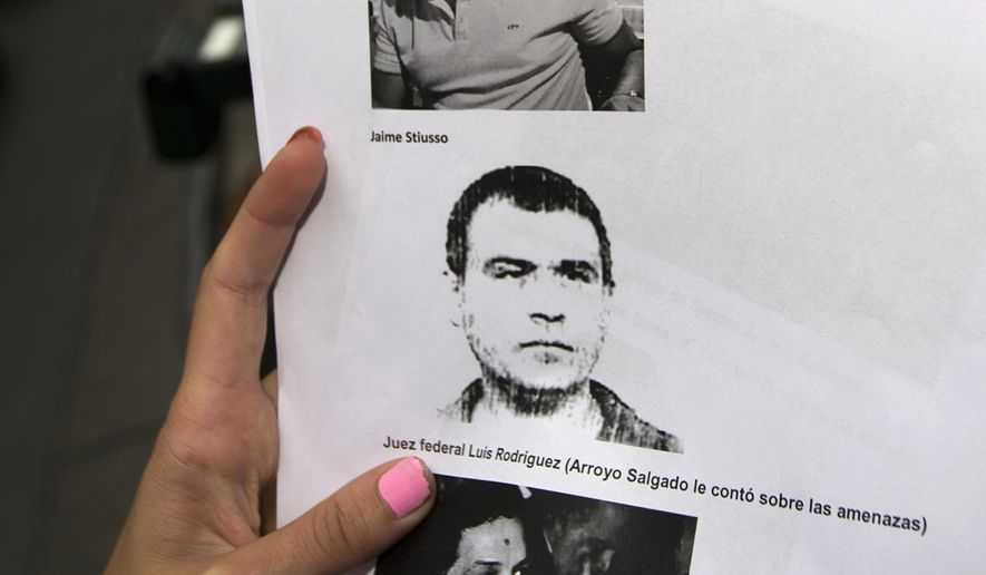"""FILE - In this Feb. 5, 2015 file photo, a reporter holds a copy of a photo of Antonio """"Jaime"""" Stiuso, one of the country's most enigmatic spy chiefs, outside the prosecutor's office in Buenos Aires, Argentina. The Argentine government said on Wednesday, Oct. 7, 2015 that the former spymaster it wants to question in the mysterious death of a prosecutor traveled to the U.S. on an Italian passport. President Cristina Fernandez expressed frustration with the U.S. over Stiuso's whereabouts and said American officials had not answered requests to locate him. (AP Photo/Rodrigo Abd, File)"""