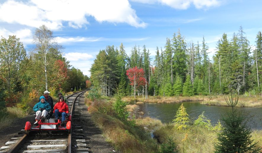 In this photo taken Thursday, Oct. 1, 2015, a group of people pedal a rail bike past a pond during a six-mile tour between Saranac Lake, N.Y. and Lake Clear, with Adirondack Rail Explorers, a business launched this summer by Alex Catchpoole and his wife Mary-Joy Lu. The future of the rail-biking enterprise is in doubt as the state has proposed removing the deteriorating tracks and building a multi-use trail that would be used mainly by bicyclists in summer and snowmobilers in winter. (AP Photo/Mary Esch)