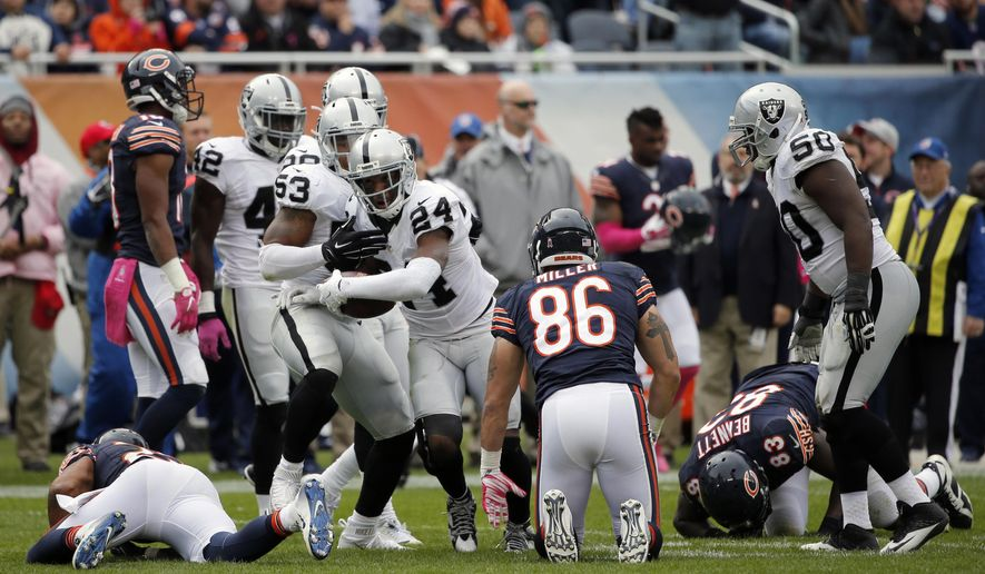 Oakland Raiders free safety Charles Woodson (24) celebrates after intercepting a pass during the second half of an NFL football game against the Chicago Bears, Sunday, Oct. 4, 2015, in Chicago. (AP Photo/Charles Rex Arbogast)