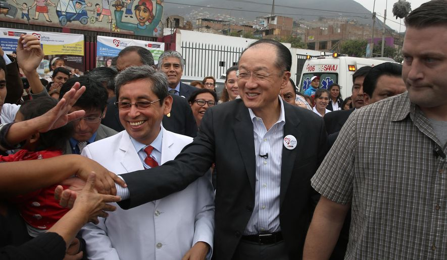 World Bank President Jim Yong Kim shakes hands with people as he walks with Peru's Health Minister Anibal Velasquez in the poor neighborhood Carabayllo in Lima, Peru, Monday, Oct. 5, 2015. Jim Yong Kim, who worked in Carabayllo more than 15 years ago with patients who had drug resistant TB, is in Peru for the annual meetings of the World Bank Group and the International Monetary Fund, Oct. 6-11. (AP Photo/Martin Mejia)
