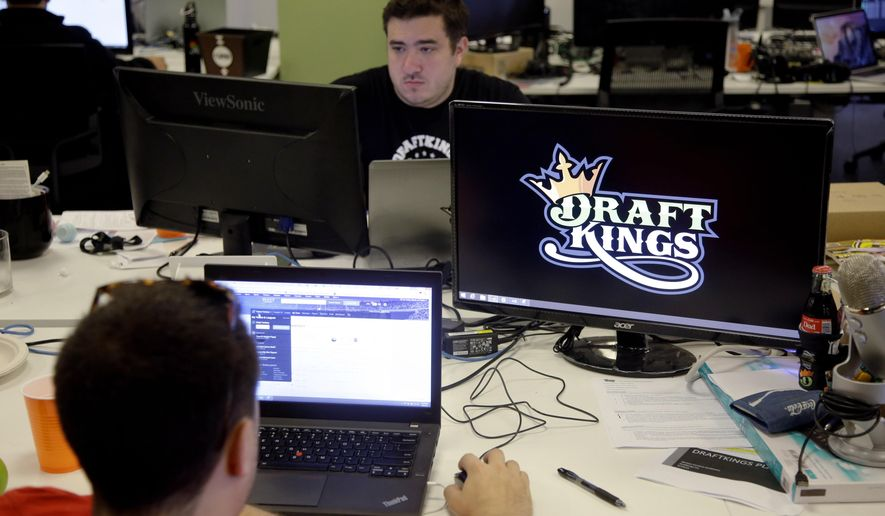 FILE- In this Sept. 9, 2015, file photo, Len Don Diego, marketing manager for content at DraftKings, a daily fantasy sports company, works at his station at the company's offices in Boston.  New York's attorney general has sent letters to daily fantasy sports websites DraftKings and FanDuel demanding they turn over details of any investigations into their employees on Tuesday, Oct. 6, 2015. (AP Photo/Stephan Savoia, File)