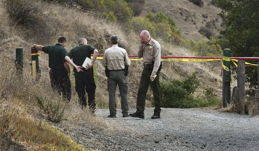 In this Tuesday, Oct. 6, 2015, photo, Marin County Sheriff's members investigate a homicide near the top of White's Hill on Old Railroad Grade near Fairfax, Calif. A tantra teacher who made DVDs on yoga for lovers and taught classes at a clothing-optional retreat was found shot to death on a hiking trail in Northern California, still holding onto the leash of his wounded dog, authorities said. Detectives are looking for three people of interest in the killing of Steve Carter, 67.(Robert Tong/Marin Independent Journal via AP)