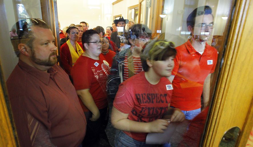 Gwen Schablik, second from the left, tries to enter the Blount County courthouse with others as they attend a meeting to speak against a resolution proposed by Commissioner Karen Miller at the Blount County courthouse Tuesday, Oct. 6, 2015, in Maryville, Tenn. The resolution asking God to have mercy on a Tennessee county for issuing marriage licenses to same-sex couples apparently didn't have a prayer of being considered Tuesday. (AP Photo/Wade Payne)